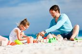 Father and daughter at beach playing with sand during summer vacation