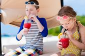 Kids at luxury resort relaxing at beach cabana and drinking tropical juices