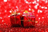 Decorated red holiday gifts on glitter background