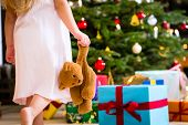Girl wearing night dress with Christmas gift and teddy bear