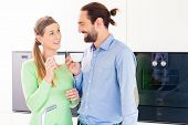 Couple drinking cup of coffee in domestic kitchen