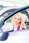 Woman buying new car at dealership showing key