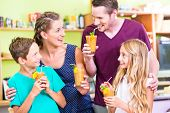 Parents and children drinking smoothie or juice in domestic kitchen