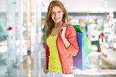 Portrait of casual girl with shopping bags looking at camera