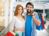 Portrait of young couple with paperbags looking at camera after shopping