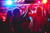 Group of happy friends dancing in nightclub