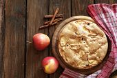 Closeup photo of holiday apple pie on rustic wooden background, top view point