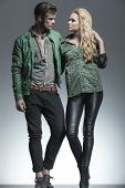 Full length picture of a young fashion couple holding each other, looking away from the camera.