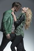 Blonde fashion woman pulling her lovers jacket while he is holding his thumb in his pocket.