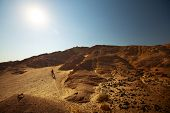Woman with bicycle crossing desert with rocks