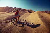 Woman with bicycle in the desert