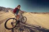 Lady with bicycle in the desert at sunny day