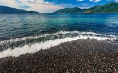 Beautiful Crystal Clear Sea With Black Pebble Beach