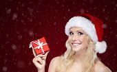 Woman in Christmas cap hands present wrapped with red paper,on snowy background