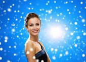people, holidays, christmas and people concept - smiling woman in evening dress over blue snowy background