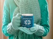 Woman holding winter cup close up on light background. Woman hands in teal gloves holding a cozy mug with hot cocoa, tea or coffee and a candy cane. Winter and Christmas time concept.