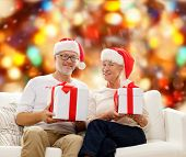 family, holidays, christmas, age and people concept - happy senior couple in santa helper hats with gift boxes over red lights background