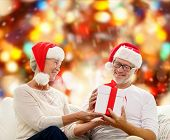 family, holidays, christmas, age and people concept - happy senior couple in santa helper hats with gift box over red lights background
