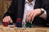 pic of shiting  - red blue and shite chips in piles near player sitting at table  in casino with selective focus - JPG