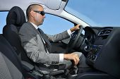 a young man wearing a suit and sunglasses driving a car with manual transmission