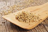 foto of sesame seed  - sesame seeds in a wooden spatula on a rustic wooden table - JPG