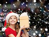christmas, holidays, childhood and people concept - smiling girl in santa helper hat with gift box over snowy night city background