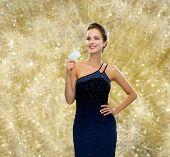 shopping, wealth, holidays and people concept - smiling woman in evening dress holding credit card over yellow lights background
