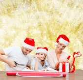 christmas, holidays, family and people concept - happy mother, father and little girl in santa helper hats with gift box and scissors over yellow lights background