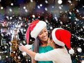 christmas, holidays, celebration, family and people concept - happy mother and little girl in santa helper hats over snowy night city background