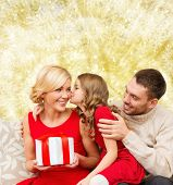 christmas, holidays, family and people concept - happy mother, father and little girl with gift box kissing over yellow lights background