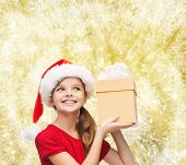 christmas, holidays, childhood and people concept - smiling girl in santa helper hat with gift box over yellow lights background
