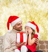 family, christmas, winter holidays and people concept - smiling daughter with closed eyes waiting for present from father over yellow lights background