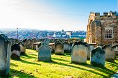 View Of St Mary's Church, Gravestones And Whitby Abbey In North Yorkshire, Uk