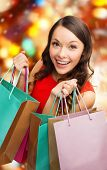 sale, gifts, christmas, holidays and people concept - smiling woman with colorful shopping bags over red lights background