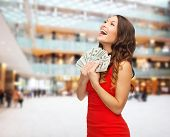 christmas, holidays, sale, banking and people concept - smiling woman in red dress with us dollar money over shopping center background