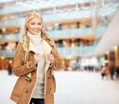 winter holidays, christmas, fashion and people concept - smiling young woman in winter clothes over shopping center background