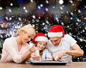 food, family, christmas, happiness and people concept - smiling family in santa helper hats with glaze and pan cooking over snowy night city background