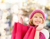 happiness, winter holidays, christmas and people concept - smiling young woman in hat and scarf with pink shopping bags over lights background