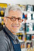 Closeup portrait of senior salesman smiling in hardware store