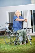 Full length of senior woman holding walking stick while sitting on wheelchair at nursing home lawn