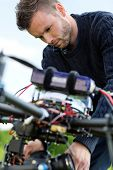 Closeup of young technician fixing camera on UAV drone in park