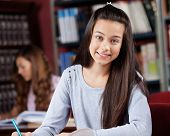 Portrait of beautiful teenage girl with female classmate in background at library