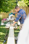 Side view of mid adult manual worker cutting wood using table saw at construction site