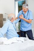 Male caretaker supporting senior man to get up from bed at nursing home