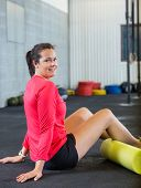 Side view portrait of smiling young woman exercising in gym