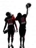 two american football players walking,rear view in silhouette shadow on white background