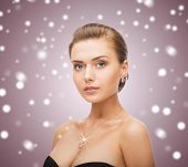 beauty, people and jewelry concept - woman wearing shiny diamond earrings and pendant
