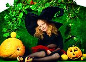 Cute little girl in a witch costume posing with pumpkins. Halloween.