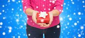 christmas, holidays and people concept - close up of woman in pink sweater holding gift box blue snowy background