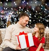 family, christmas, holidays and people concept -smiling father and daughter with gift box over snowy night city background